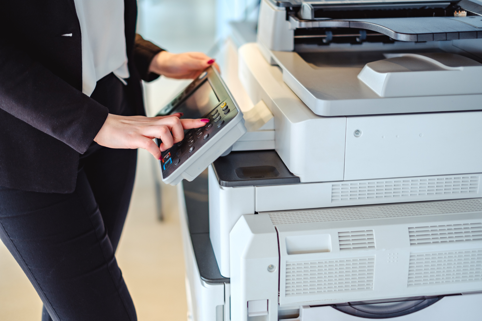 Woman using printer with managed print services in Toronto
