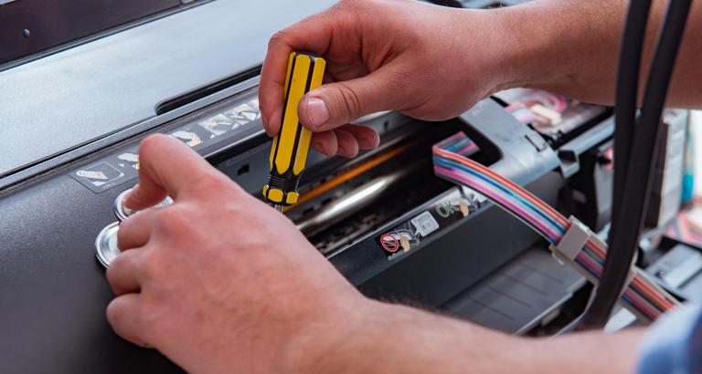Gros plan d'un réparateur réparant une imprimante cassée
