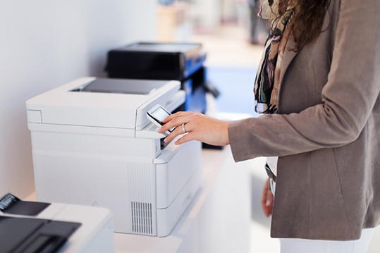 Employee approaching one of the printers within a network