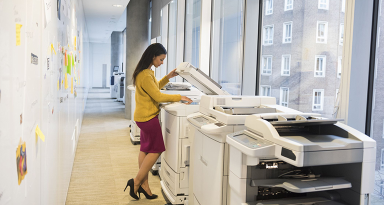 An employee walking over to one of the network printers in the office