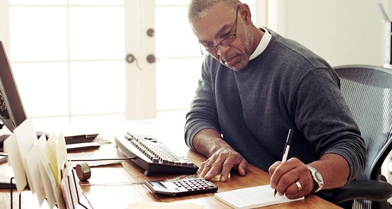 A man works from home with a desktop computer, calculator and notepad