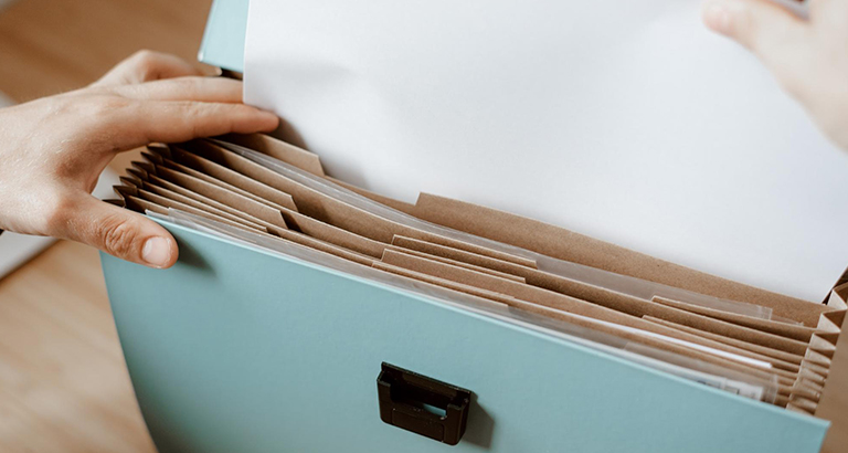 Close up of someone putting a document inside an expandable envelope