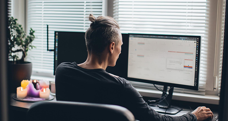 A man working from a home office with two monitors