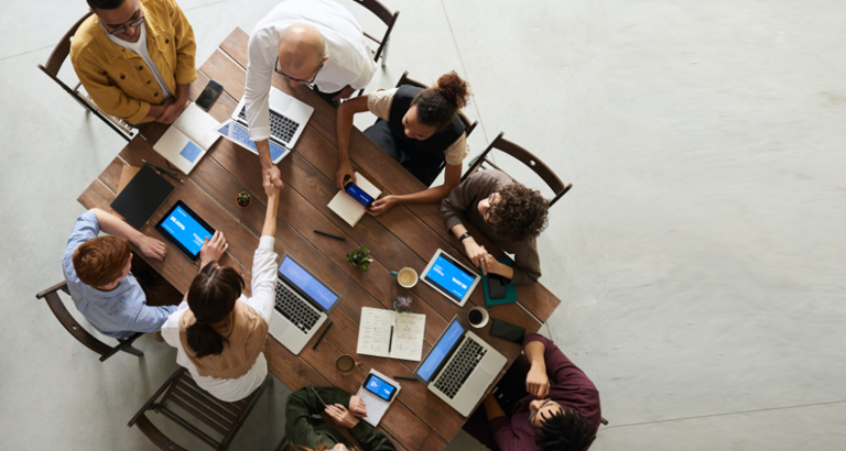 Overhead shot of a team having a meeting with their laptops and other digital devices