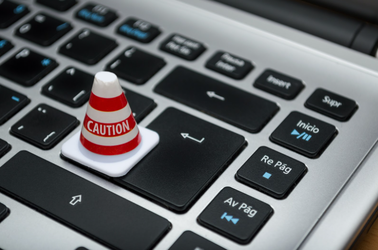 A small caution sign placed over the enter key of a laptop