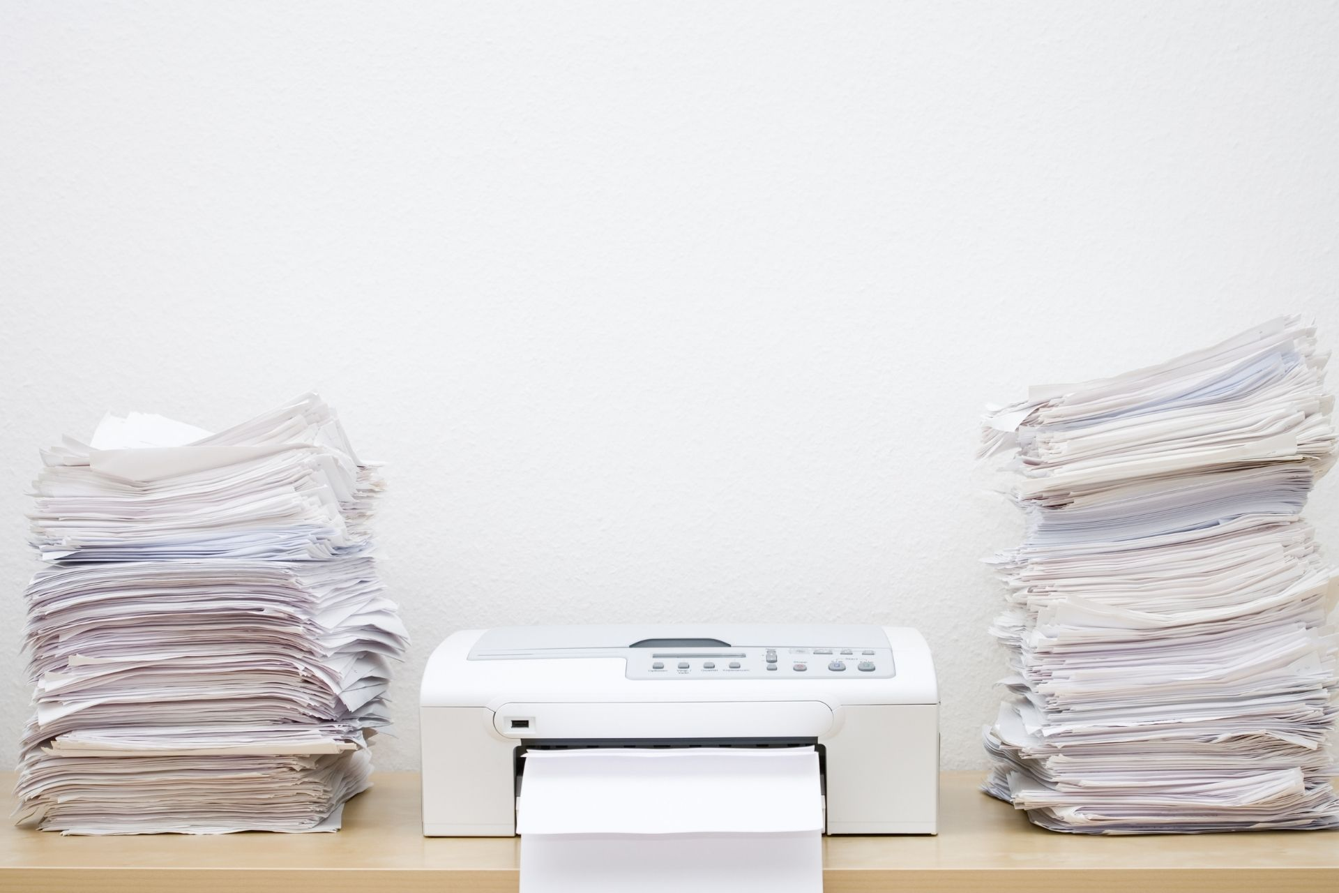 A printer and stacks of paper on a table