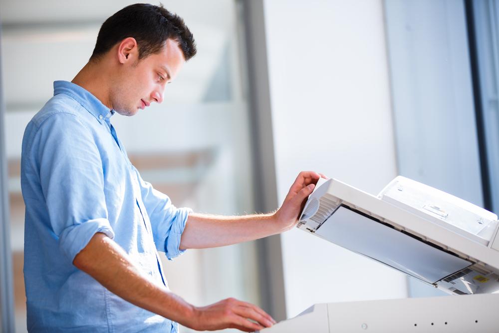Young man using a copying machine