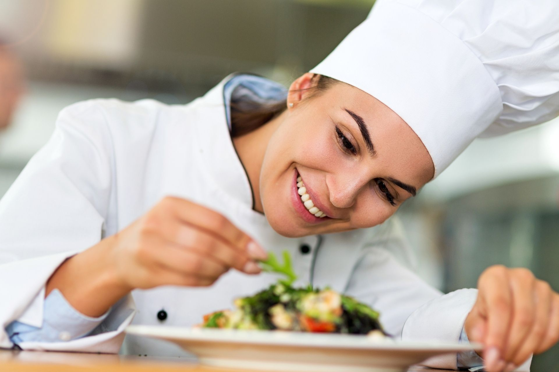 A chef garnishing a plate of food