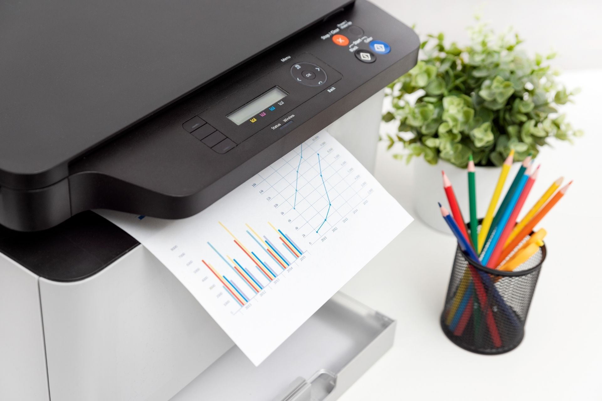 A printer next to a pencil holder and a plant
