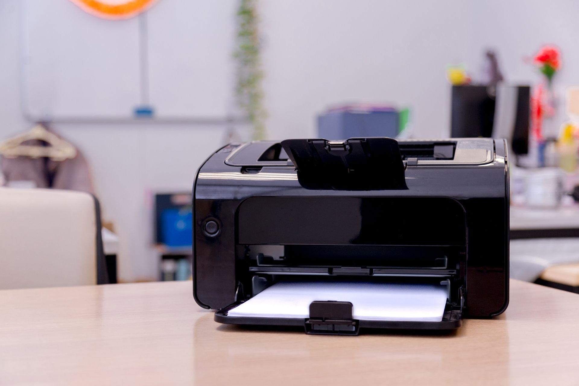 A black printer on an office desk