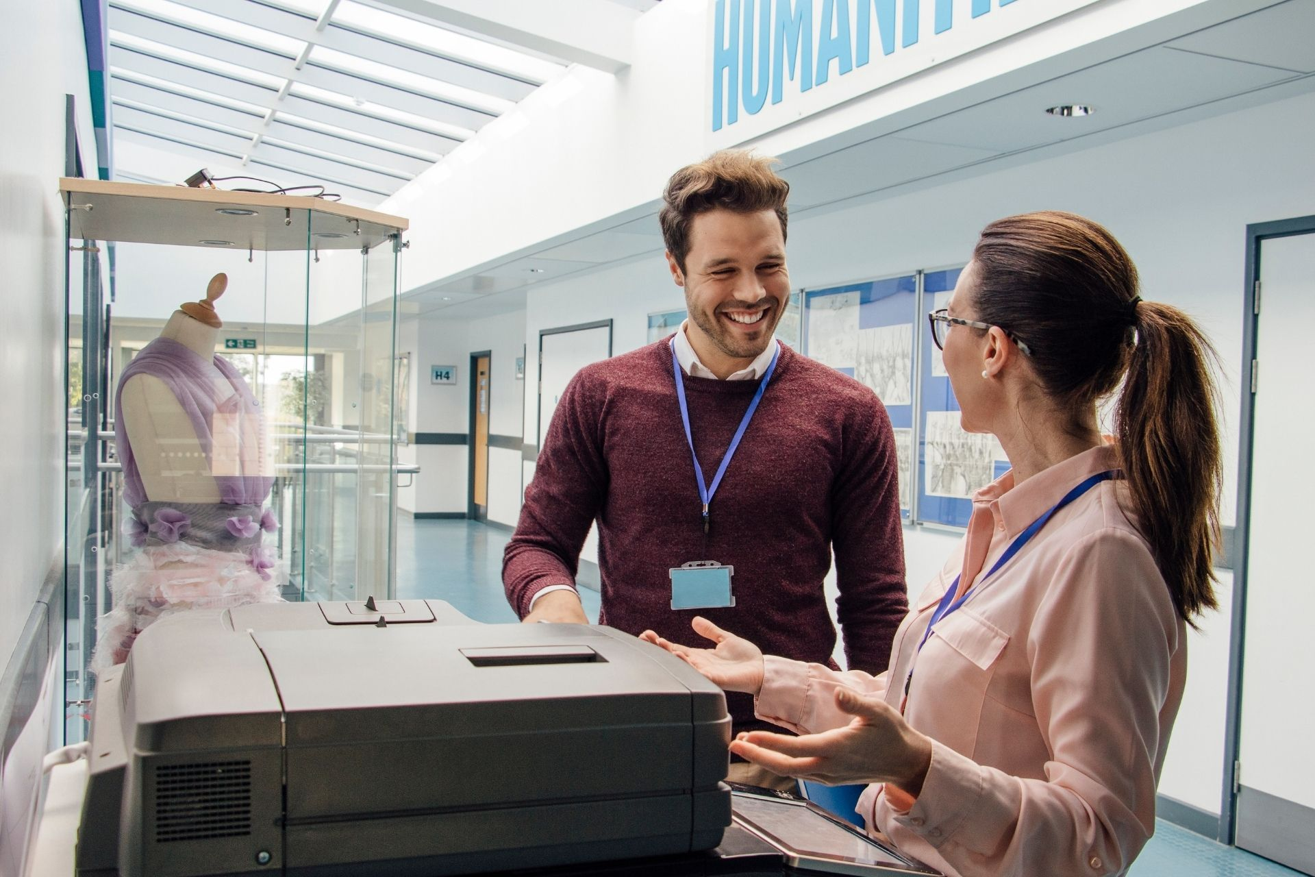 Two people standing next to a copier machine