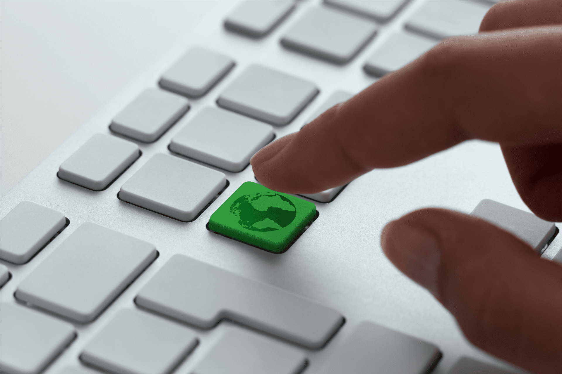A person pressing a green key that represents sustainability
